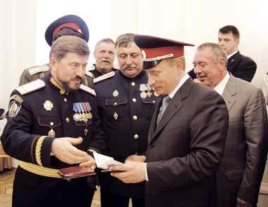 Атаман, казачий генерал Виктор Водолацкий  вручает Президенту РФ Владимиру Путину удостоверение казачьего полковника